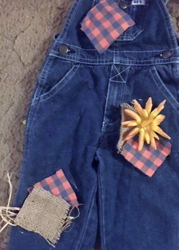 Easy DIY toddler scarecrow costume. Arrange the patches on the overalls to their desired position.